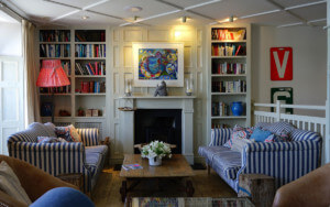 outsourcing your property management, a neatly furnished living room with sofas and artistic decor and well stocked book shelves